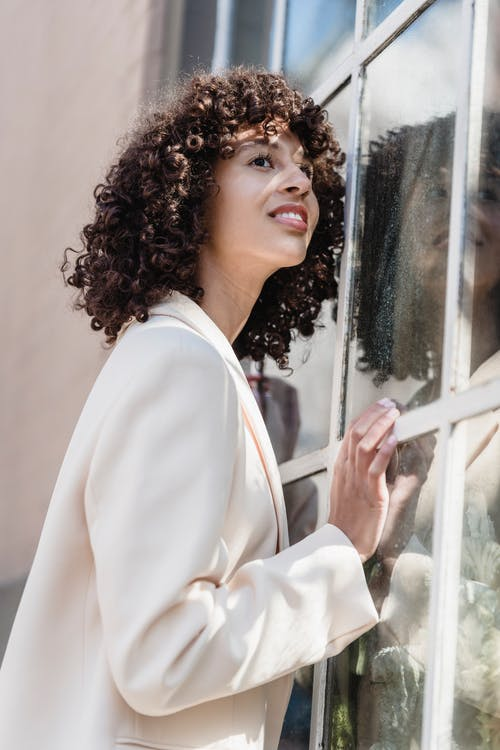 Side view of charming ethnic female with curly hair looking away against window in sunny town