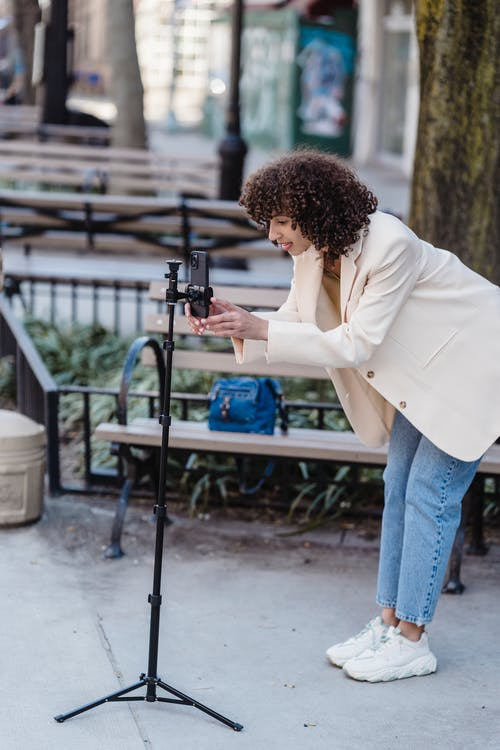 Attentive ethnic blogger with smartphone on urban pavement