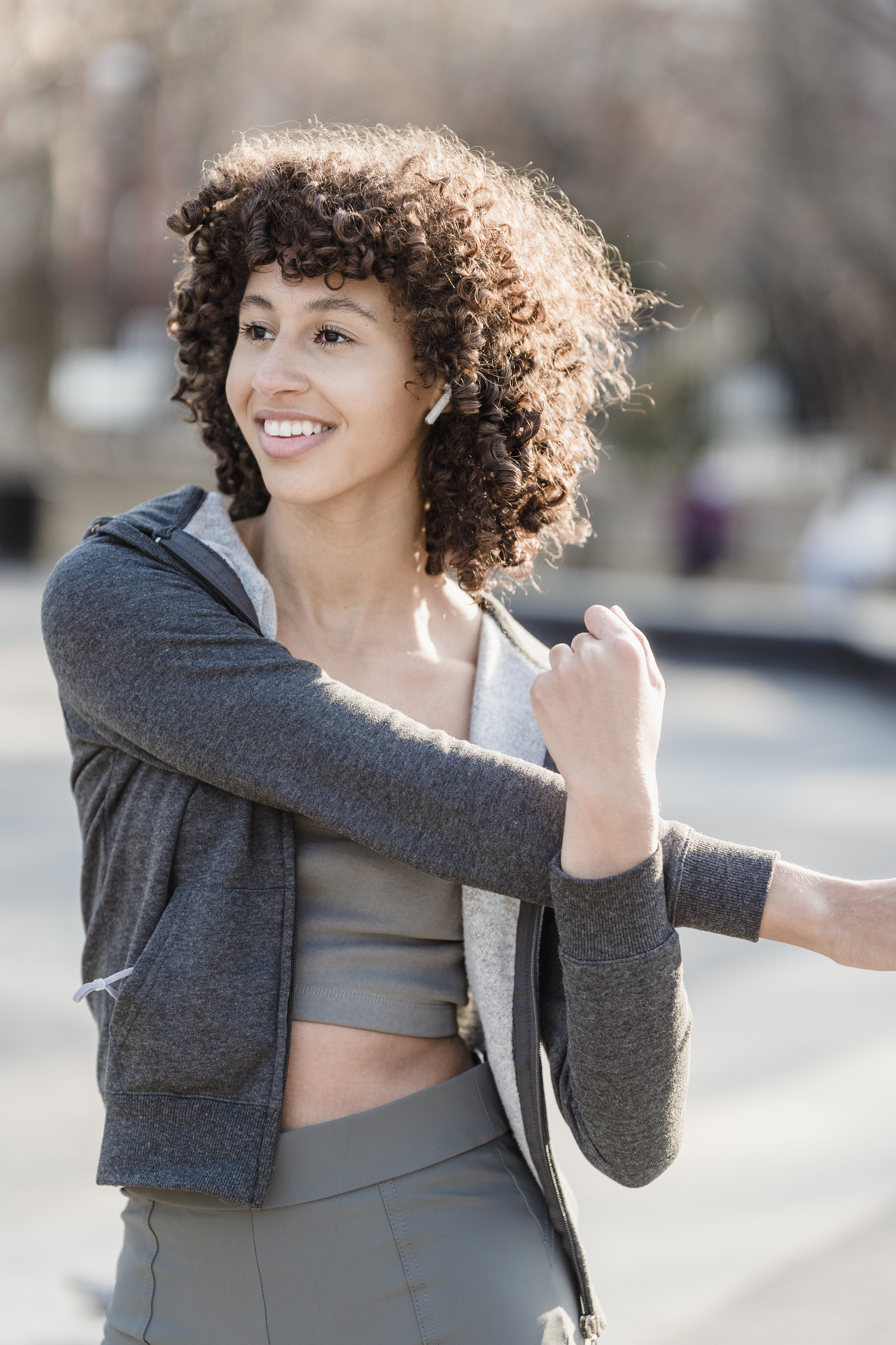 smiling ethnic sportswoman in earbuds working out on street