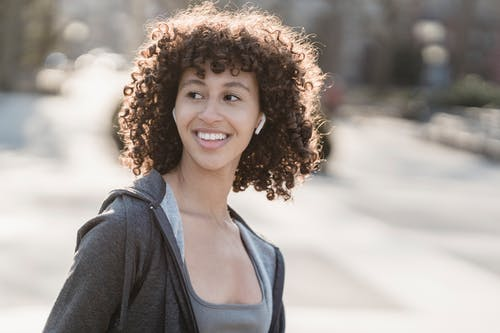 Smiling ethnic sportswoman in earbuds on street
