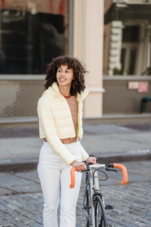 Charming ethnic female in padded jacket with bike strolling on tiled walkway while looking away in town