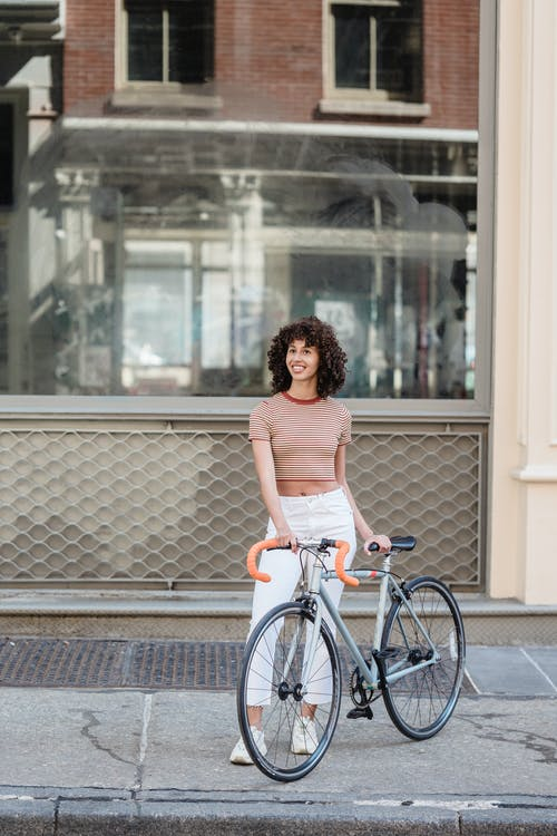Smiling ethnic woman with bicycle standing on street