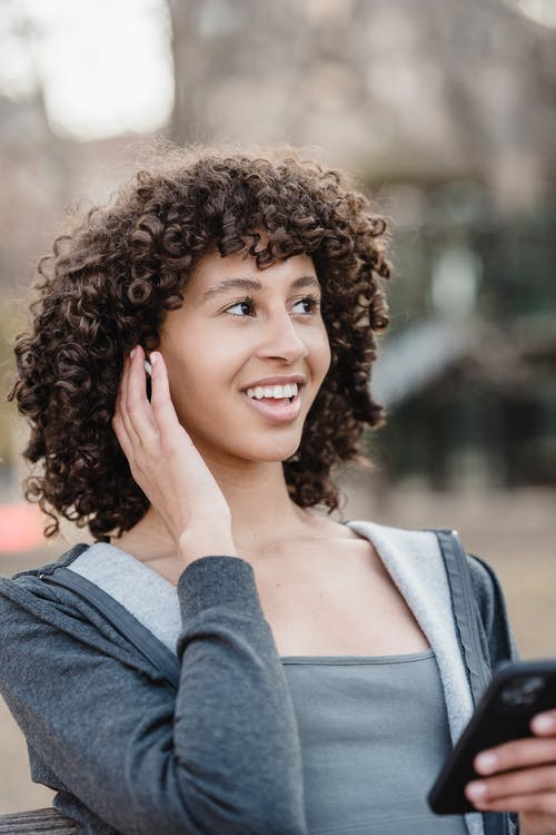 Positive ethnic woman using smartphone and earbuds for phone call