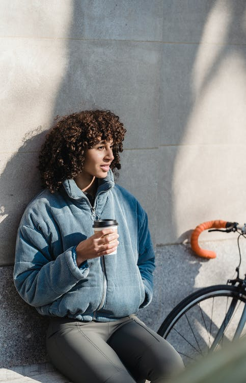 Positive ethnic woman with cup of takeaway coffee
