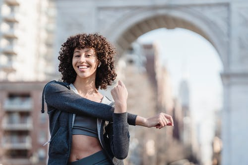 Delighted young ethnic female with Afro curls wearing sportswear stretching arms and listening to music in TWS earbuds while preparing for training