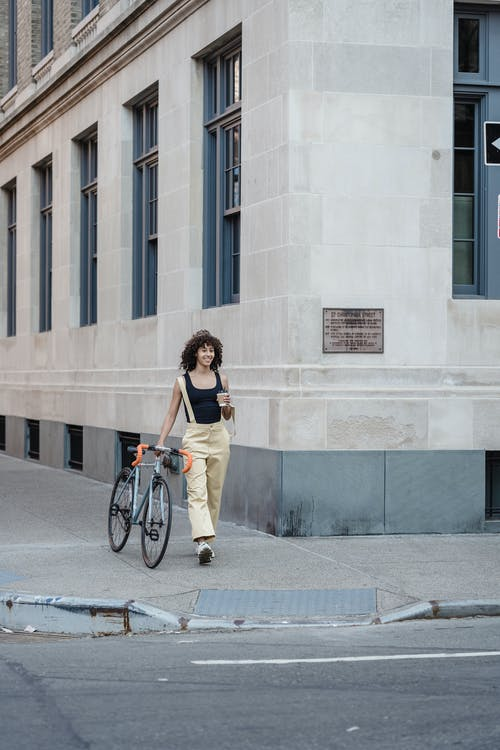 Full body of smiling ethnic female pedestrian having takeaway coffee while leading bicycle on sidewalk to road