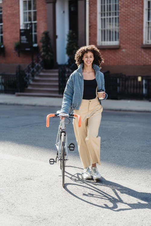 Full body of smiling ethnic female with cup of takeaway beverage crossing road with bicycle