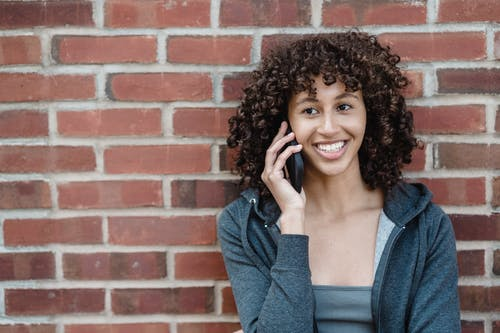 Smiling ethnic woman speaking on smartphone near brick wall