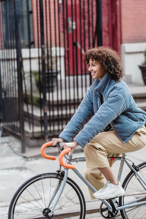 Side view of smiling ethnic female in casual outfit riding bicycle on city street