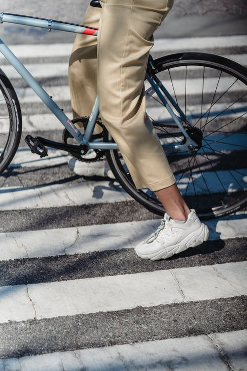 Active crop anonymous female in pants and sneakers riding bicycle on asphalt pedestrian crossing on street with sunlight in city