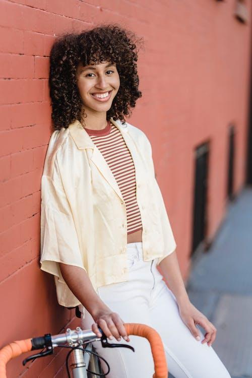 Kobieta W Białej Koszuli Zapinanej Na Guziki, Opierając Się Na ścianie Z Czerwonej Cegły