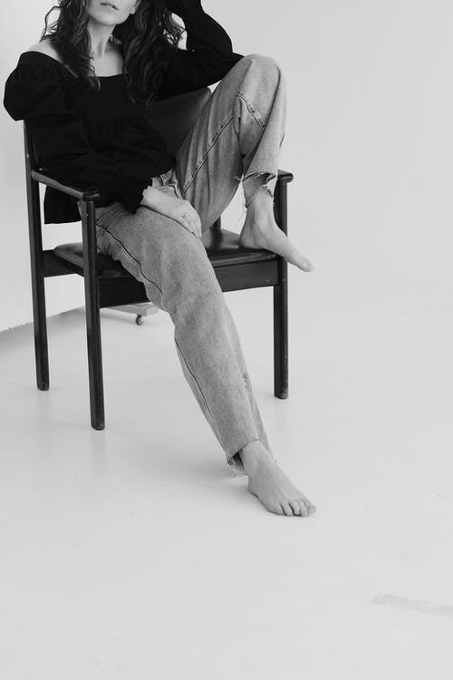 Black and white of crop unrecognizable self assured lady with long dark hair in stylish apparel leaning on hand and touching head while relaxing on chair in light studio