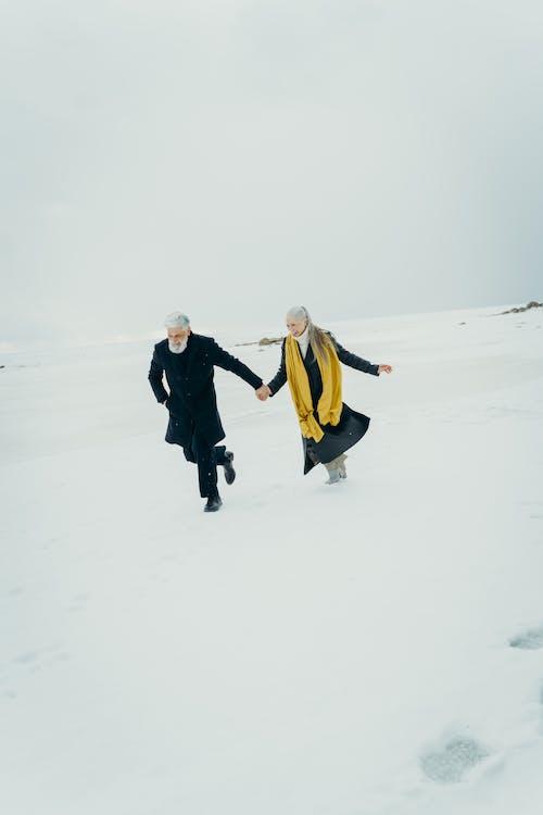 Elderly Couple Holding Hands in a Snowy Field