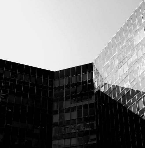 Black and white of contemporary building with glass walls under cloudless sky in sunny day