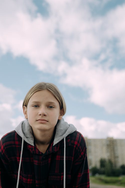 Close-Up Shot of a Girl in Hoodie Looking at Camera
