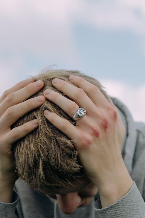 Woman in Gray Long Sleeve Shirt Wearing Silver Ring