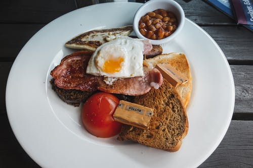 From above of toasted bread with fried bacon and egg served on white table with tomato and beans on wooden table