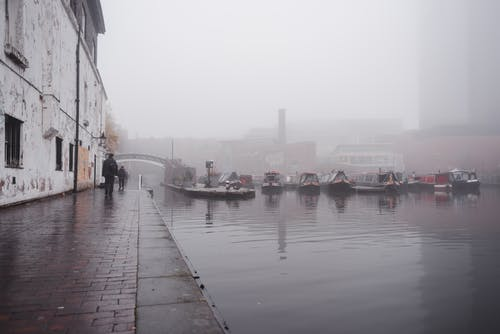 Many boats moored on calm water surface near paved waterfront with people walking near shabby building in town on foggy weather