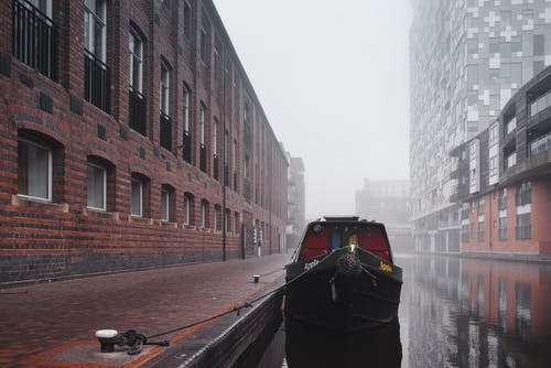 Boat moored on still water surface of channel near paved sidewalk between residential houses with windows in misty weather in city