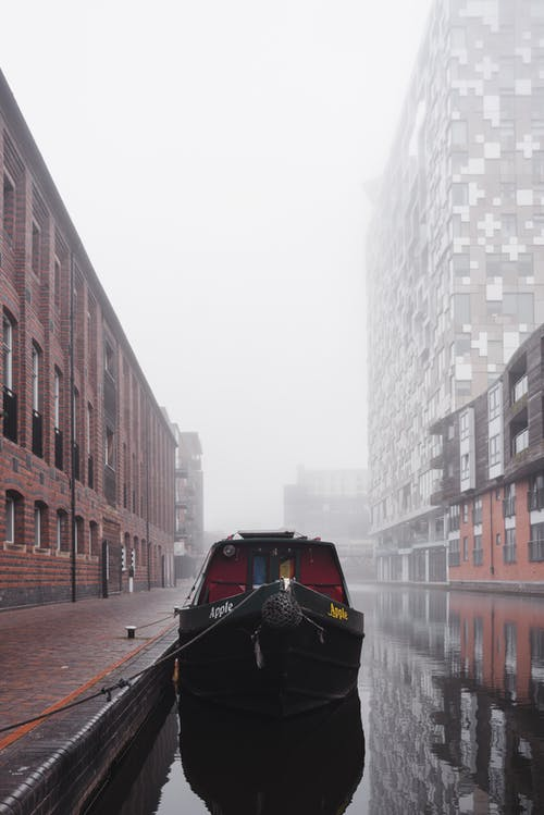 Boat moored on calm water of channel between residential buildings located on street in city against cloudless sky in foggy weather