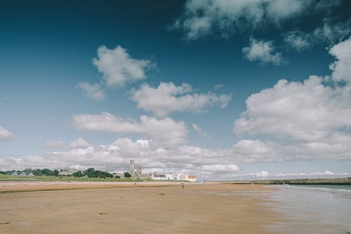 Wet sandy coast washed by river in coastal area against blue sky with clouds and buildings on sunny summer day