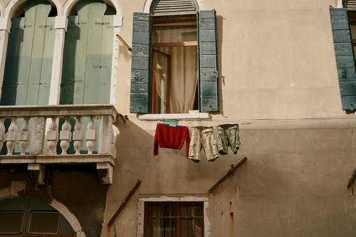 Facade of old residential building near drying laundry