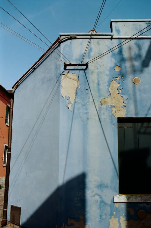 Exterior of old blue apartment building with cracked paints located in town district on sunny day