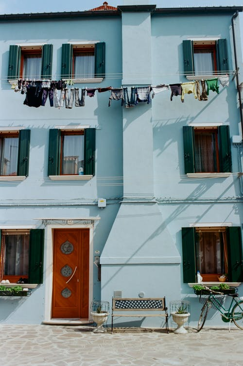 Blue residential building near drying laundry on clothesline