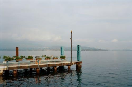 Concrete pier near rippling sea on misty day
