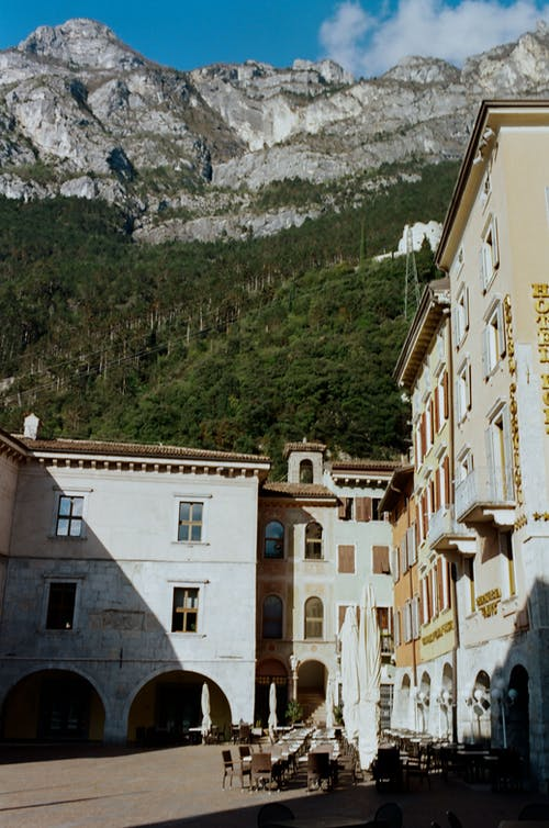 Historic old buildings with archways located on bottom of majestic massive mountain range under blue sky