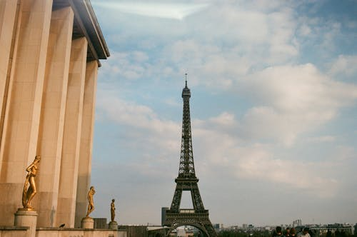 From below of observation tower and aged building exterior with sculptures under cloudy sky in Paris France