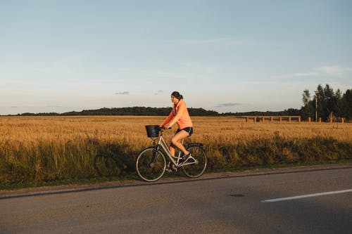 Woman riding bicycle on road against countryside field