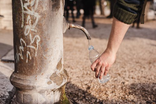 Crop person filling bottle with water from drinking fountain
