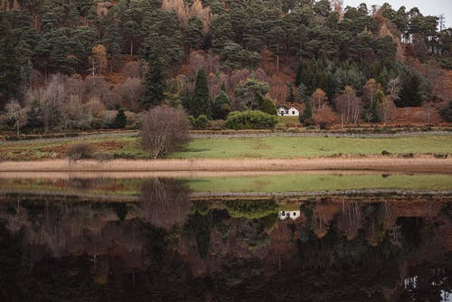 Lonely house on lawn with autumn trees reflecting in river