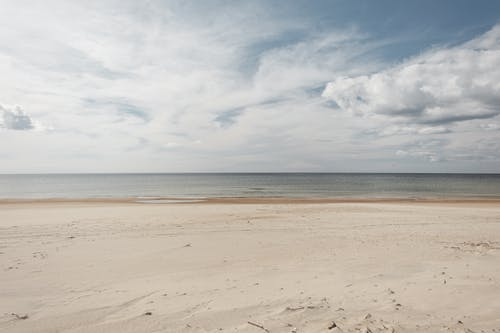 Scenery view of sandy shore against endless ocean under sky with fluffy clouds in daylight