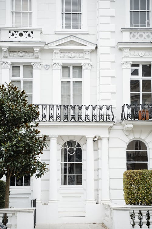 Facade of white classic styled house with windows and balconies and fences located on street with green trees in town
