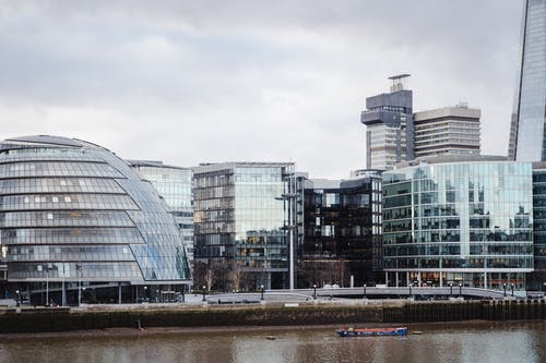 Contemporary buildings with glass walls located on street in financial district on embankment near calm Thames river in modern city