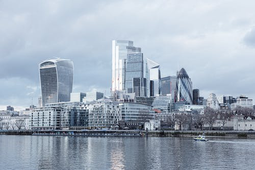 Contemporary multistory high rise business centers located on embankment with trees near Thames river in London city