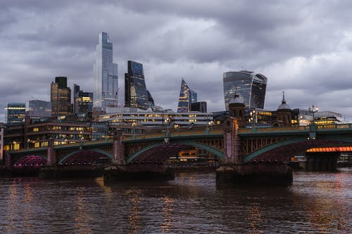 Bridge with glowing lights crossing calm Thames river located against contemporary famous multistory office buildings in London on evening time