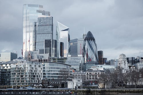 Modern multistory business centers with geometric architecture located on street against cloudy sky in downtown of London city in financial district