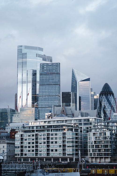 Contemporary multistory commercial office buildings with glass walls located on street in financial district of London city against cloudy sky
