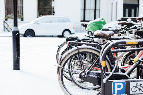 Modern bicycles parked on street covered with snow on winter day in city district