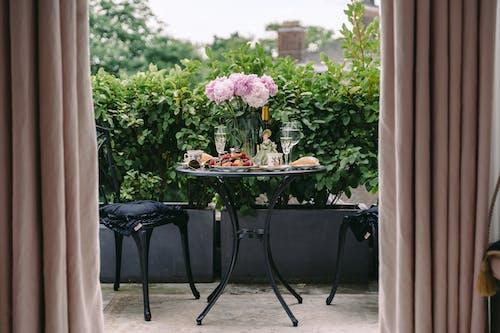 Breakfast table with elegant flowers and wineglasses on veranda of classic styled villa