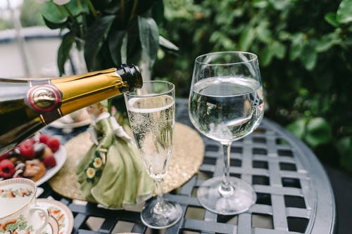 From above of unrecognizable person pouring sparkling wine into elegant crystal glass served on round table near fresh pasties with berries and coffee cups