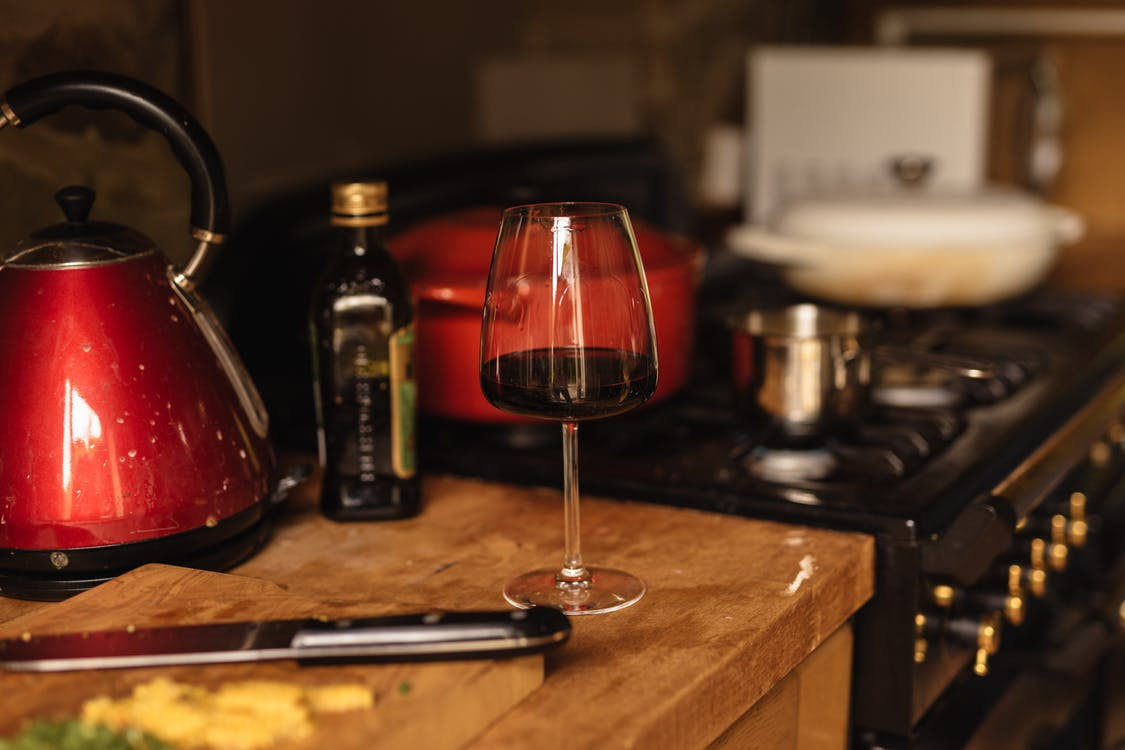 Wineglass placed on table near stone in kitchen