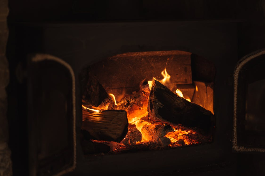 Cut wood in burning fireplace with bright orange flames in dark room of aged house