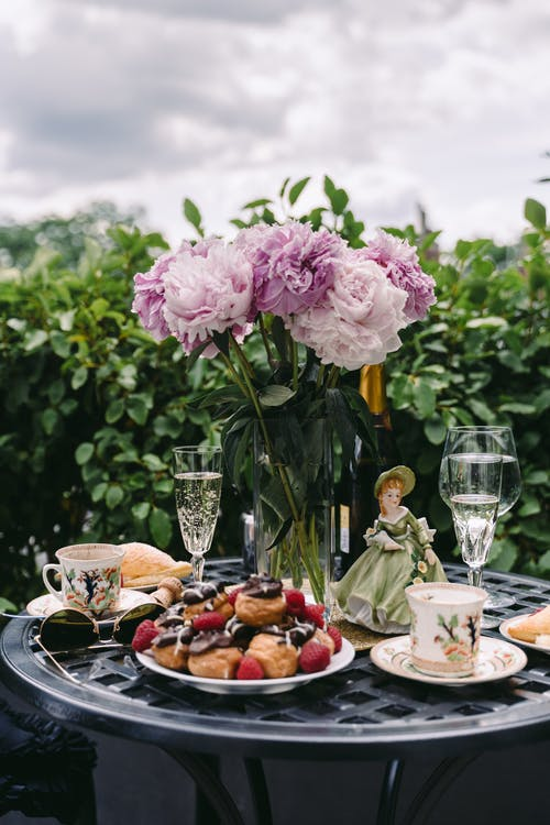 Plate of yummy pastries with wineglasses served on table with bouquet