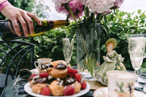 Crop faceless woman pouring champagne into glass placed on served table on veranda