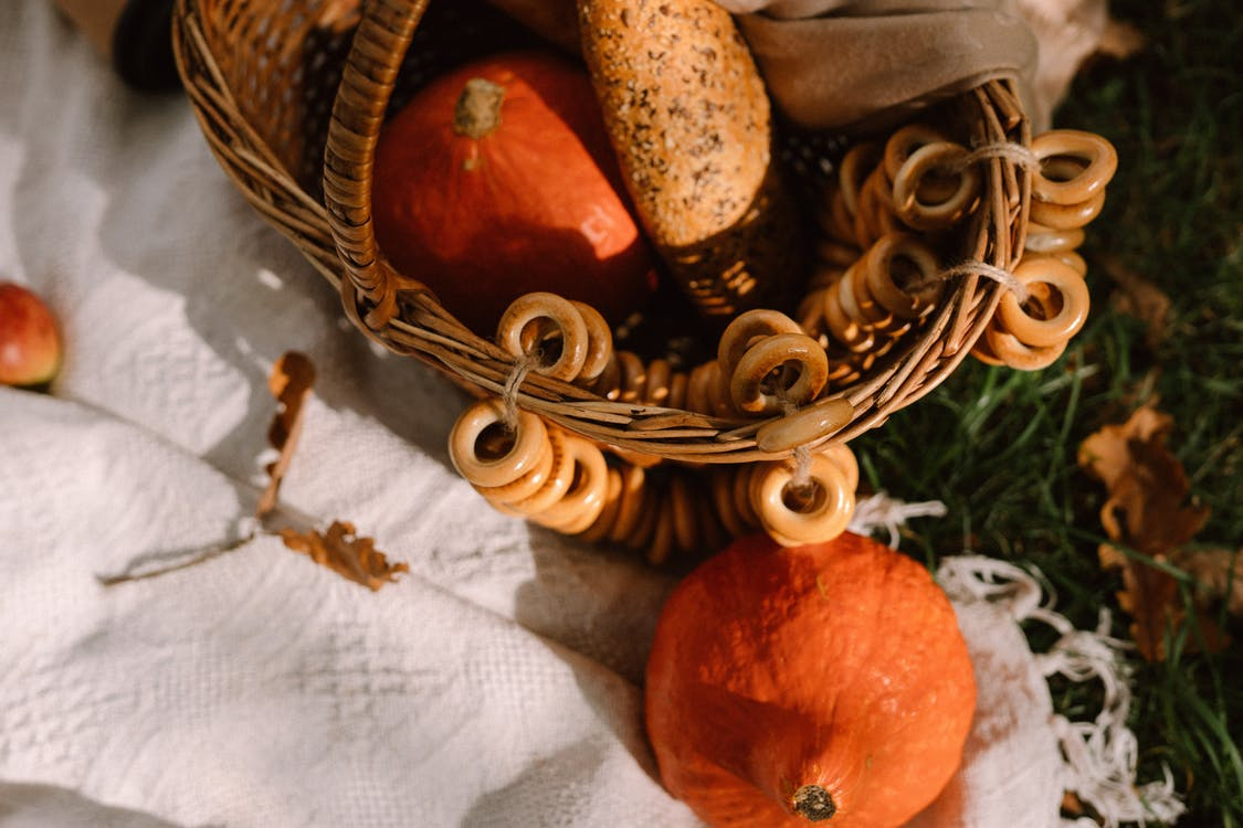 Red kuri squashes with bread in wicker basket placed on blanket on lawn in sunlight