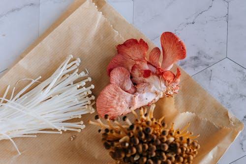 Pink oyster nameko and enoki mushrooms on paper bag